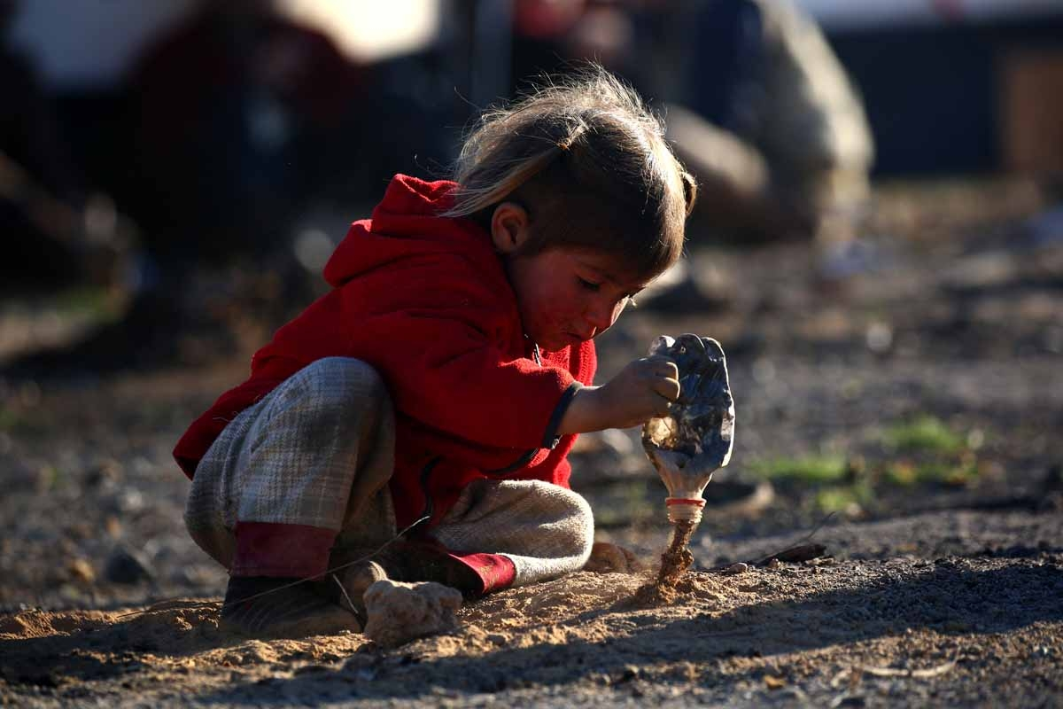 A Syrian child plays with dirt at a temporary refugee camp in the village of Ain Issa, housing people who fled Islamic State group's Syrian stronghold Raqa, some 50 kilometres (30 miles) north of the group's de facto capital on March 25, 2017.