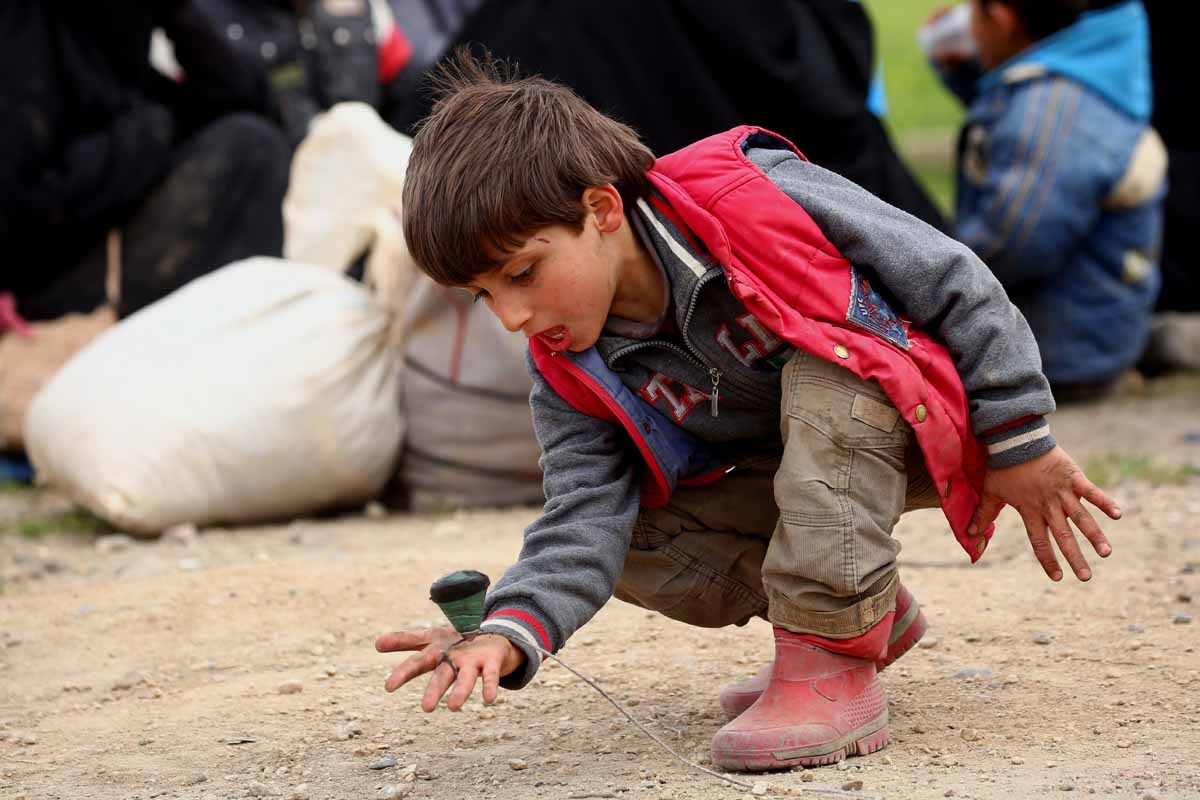 A displaced Syrian boy, who fled the Islamic State (IS) group stronghold of Raqa, plays as he arrives at a temporary camp in the village of Ain Issa on March 31, 2017.