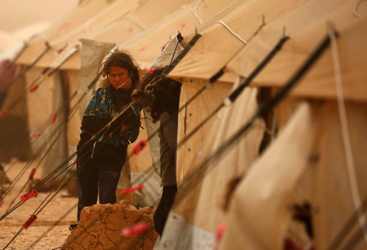 A displaced Syrian girls looks on during a sand storm at the al-Mabrouka camp in the village of Ras al-Ain on the Syria-Turkey border, where many Syrians who fled from territory held by the Islamic State (IS) group in Deir Ezzor and Raqa are taking shelte
