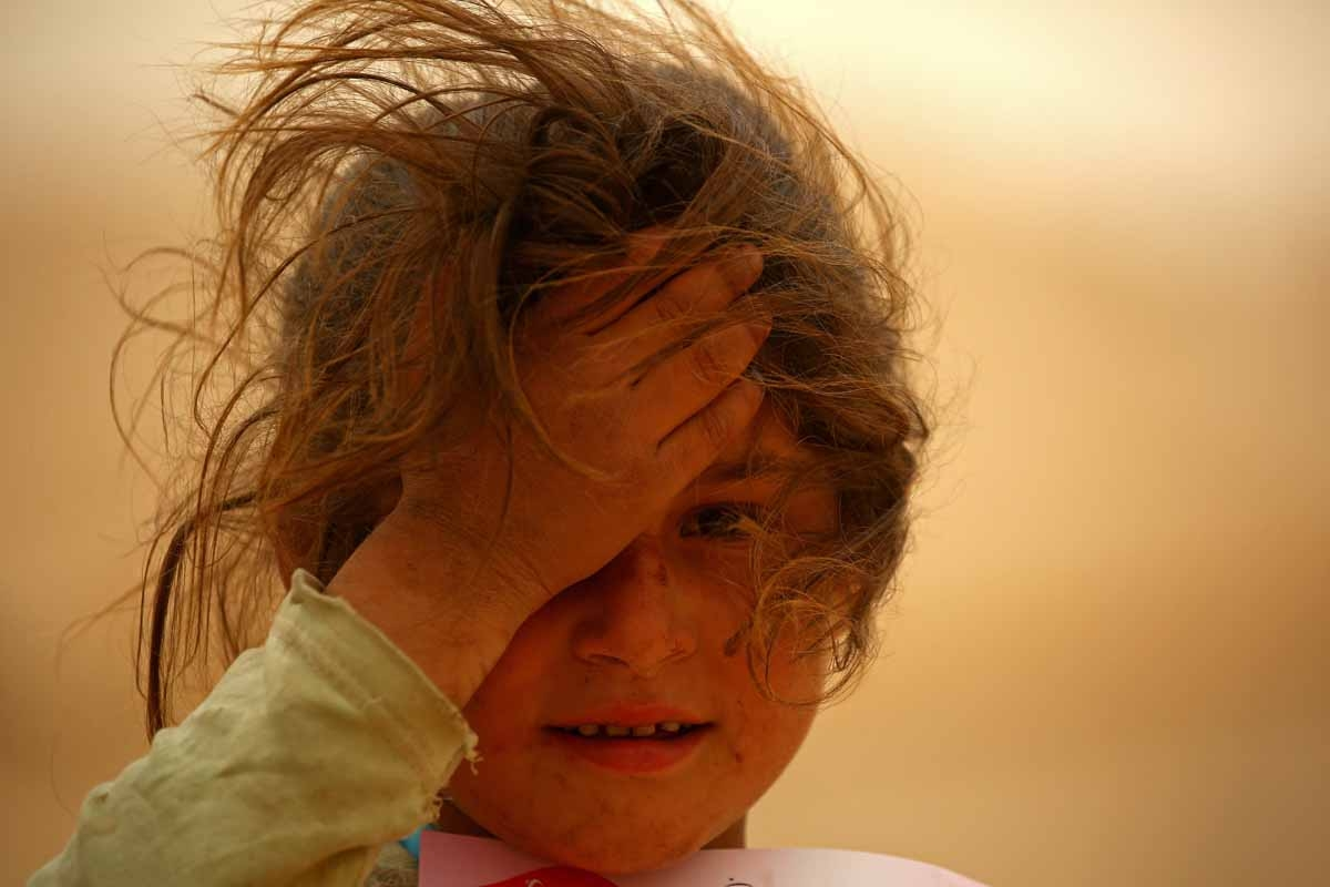 A displaced Syrian girls looks on at the al-Mabrouka camp in the village of Ras al-Ain on the Syria-Turkey border, where many Syrians who fled from territory held by the Islamic State (IS) group in Deir Ezzor and Raqa are taking shelter on April 23, 2017.