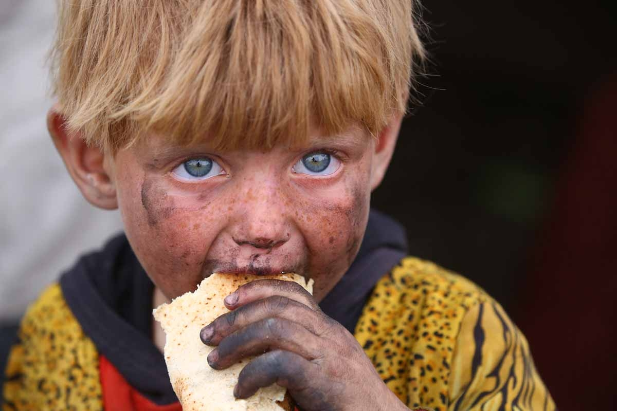 A displaced Syrian child, who fled the countryside surrounding the Islamic State (IS) group stronghold of Raqa, eats at a temporary camp in the village of Ain Issa on May 1, 2017.