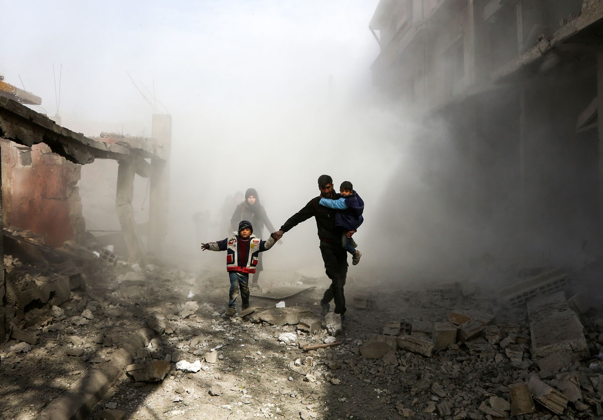 Syrian civilians flee from reported regime air strikes in the rebel-held town of Jisreen, in the besieged Eastern Ghouta region on the outskirts of the capital Damascus, on February 8, 2018.