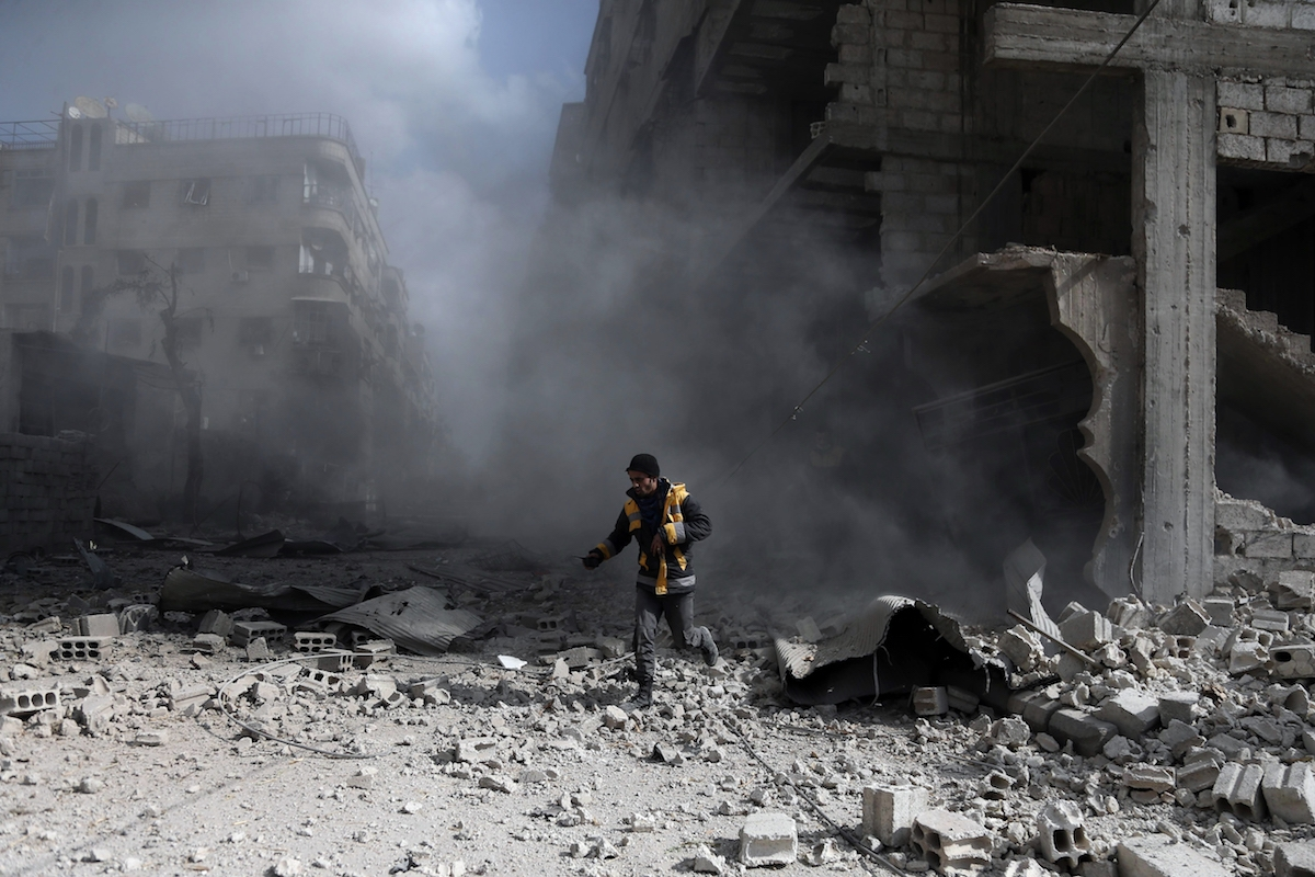 A civil Defence volunteer, known as the White Helmets, checks the site of a regime air strike in the rebel-held town of Saqba, in the besieged Eastern Ghouta region on the outskirts of the capital Damascus, on February 23, 2018.