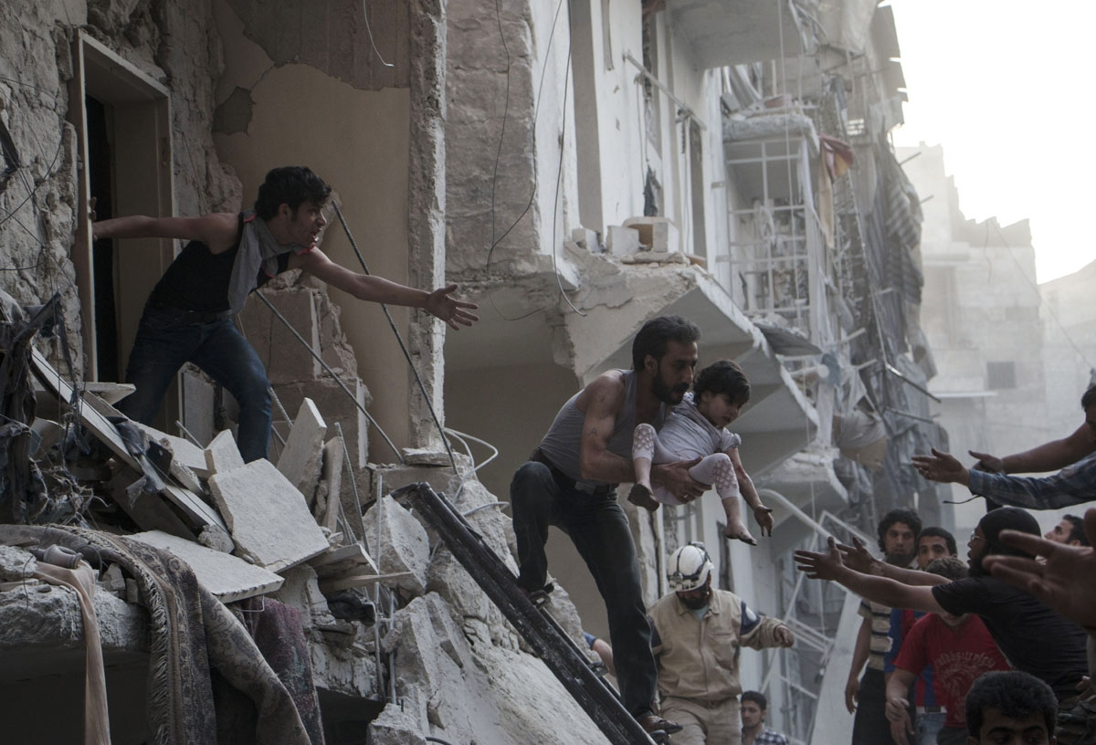 A man evacuates a child from a building following a reported barrel bomb attack by Syrian government forces on the northern Syrian city of Aleppo, on May 30, 2015. Barrel bombs dropped from regime helicopters killing more than 70 civilians in Aleppo, whil