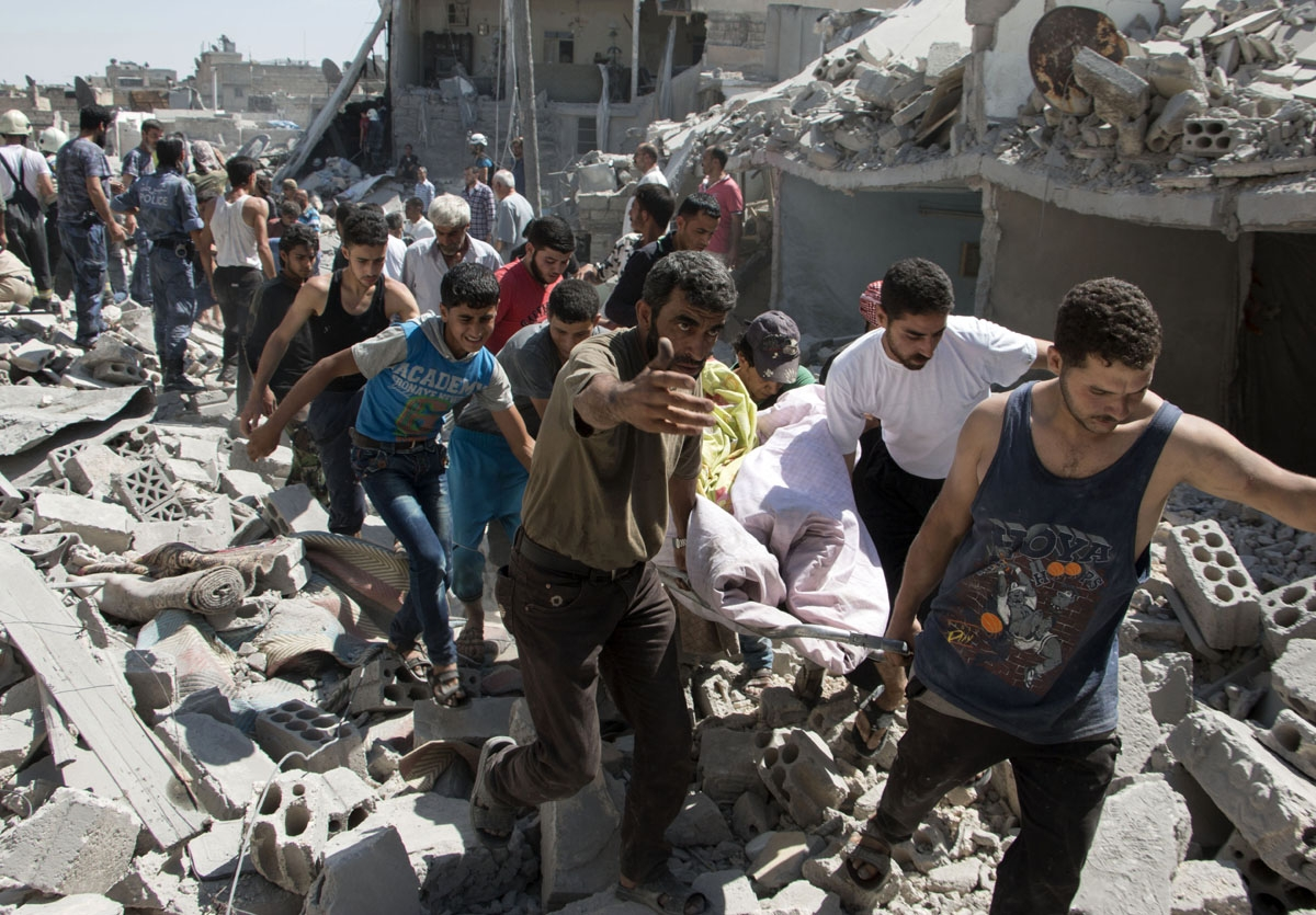 Syrians carry a body on a stretcher over the rubble after a missile fired by Syrian government forces hit a residential area in the Maghayir district in the old quarter of the northern Syrian city of Aleppo on July 21, 2015. According to the Syrian Observ