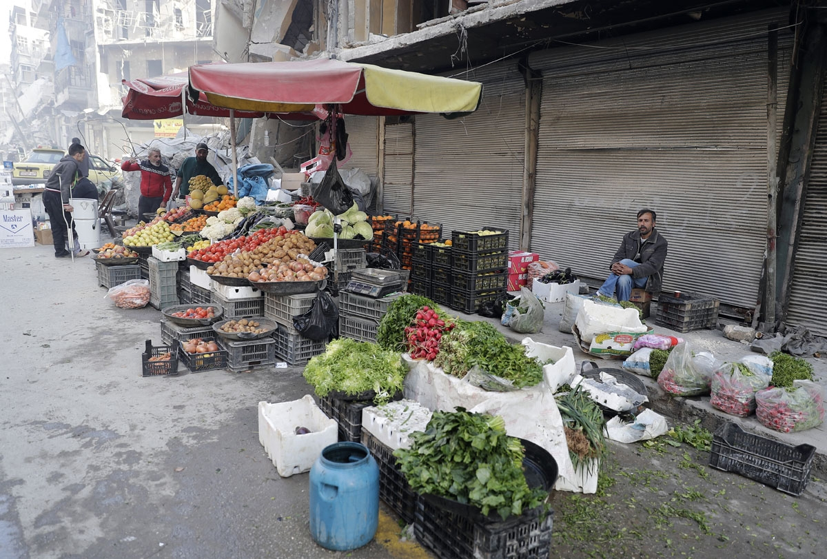 A picture taken on March 9, 2017 in the northern Syrian city of Aleppo, which was recaptured by government forces in December 2016, shows people purchasing vegetables in the formerly rebel-held al-Shaar neighbourhood.