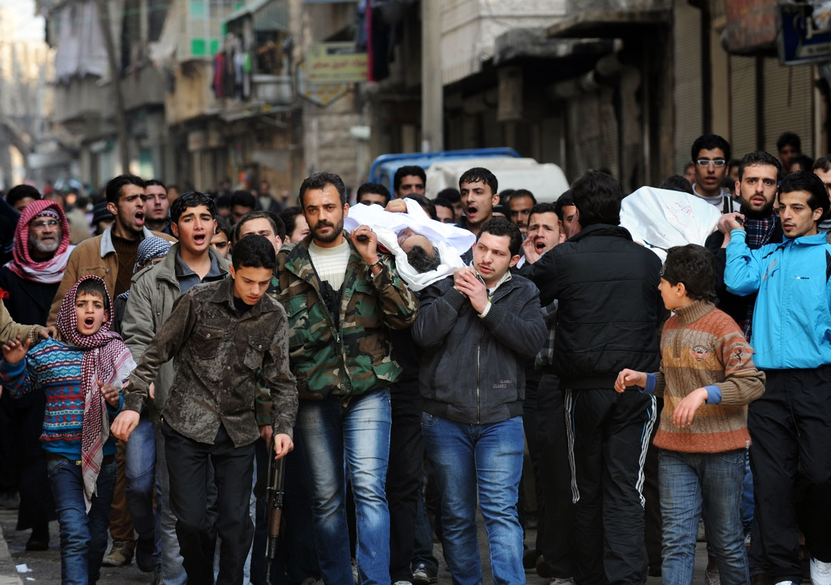 Syrians carry a body of a fighter during a funeral after Friday prayer in the northeastern city of Aleppo on February 15, 2013. Syria's army and rebels were preparing for a major battle for control of strategic airports in Aleppo, the Syrian Observatory f