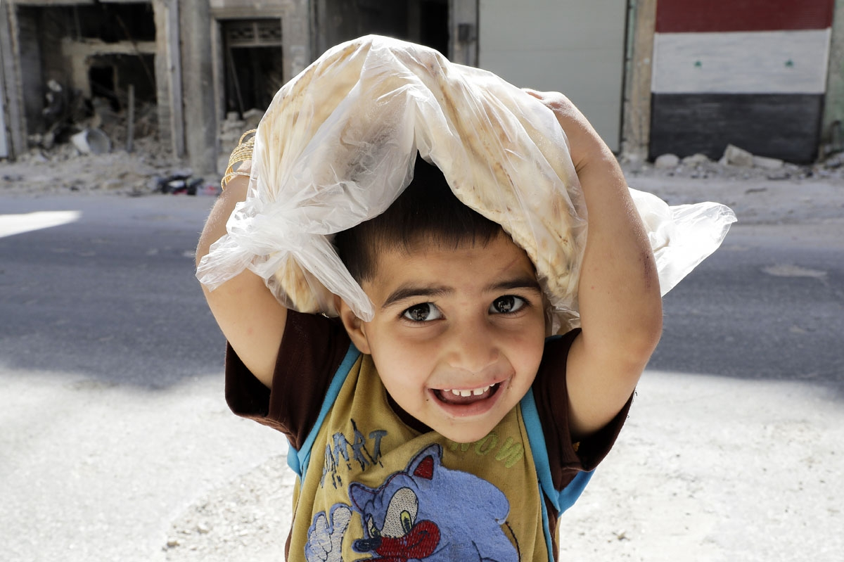 A Syrian boy carries a bag filled with bread while on his way home, in the Kallaseh district of the northern city of Aleppo, on July 5, 2017.