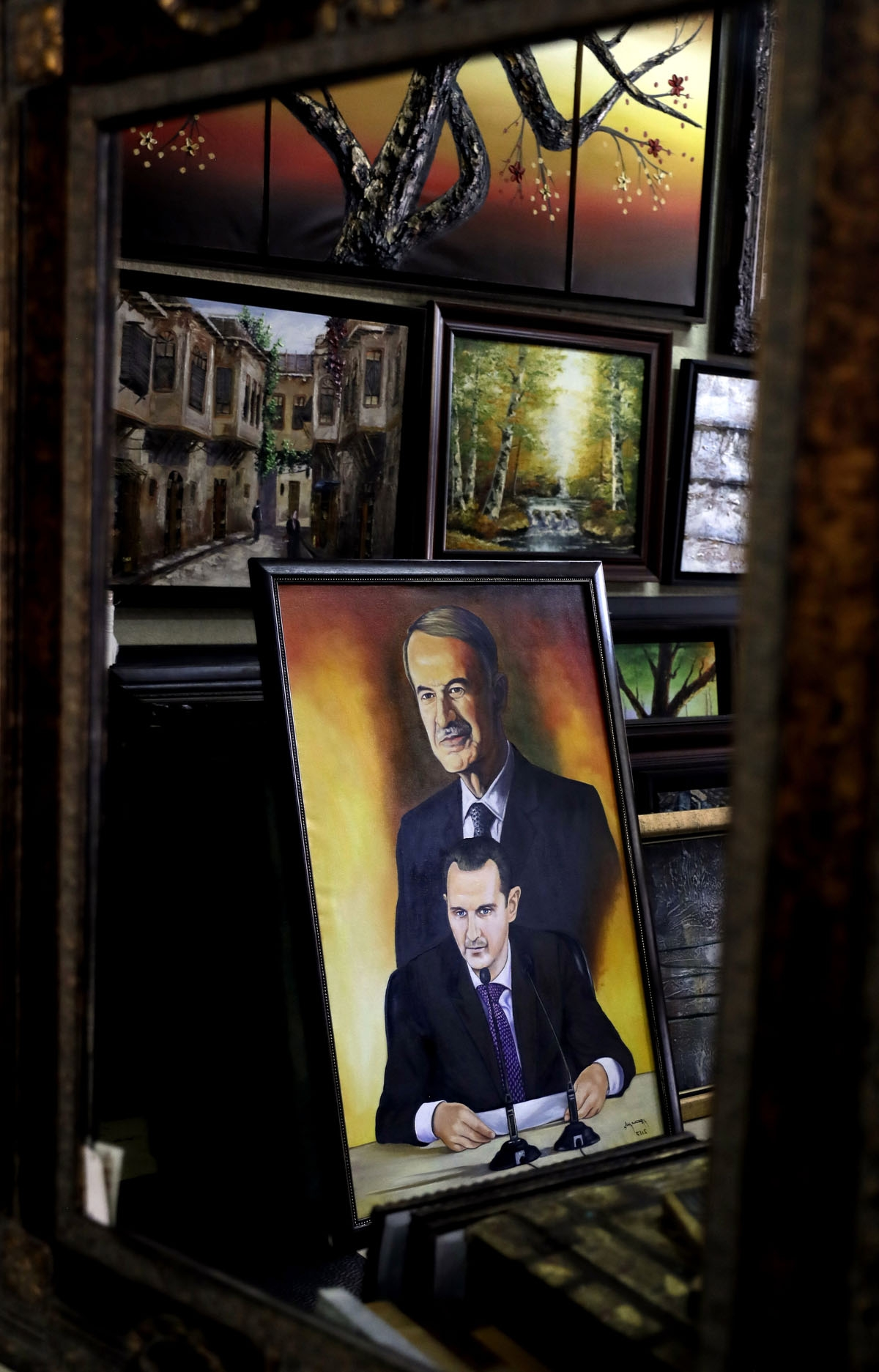 An oil painting depicting a portrait of Syrian President Bashar al-Assad and his late father Hafez al-Assad are seen at an art gallery in the capital Damascus on July 3, 2017. / AFP PHOTO / Joseph EID
