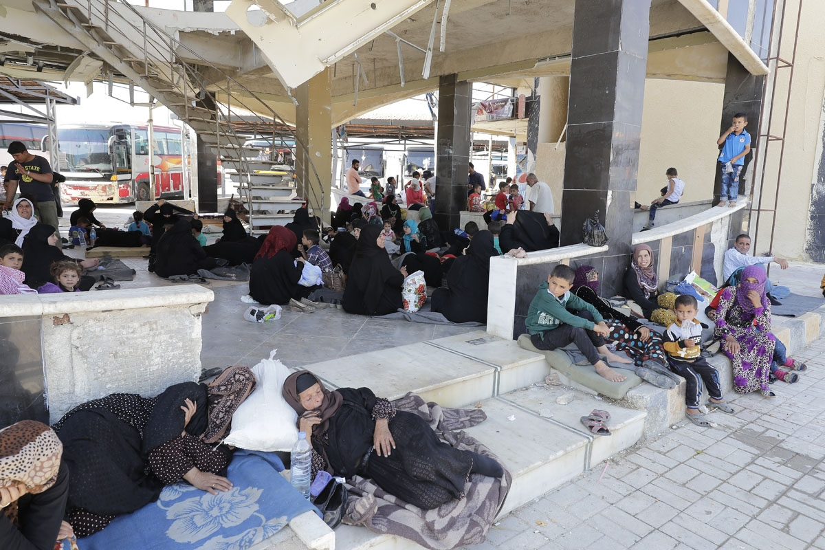 Displaced Syrians who fled with their families Islamic State controlled areas in Raqa, Deir Ezzor and Mayadeen gather at Aleppo's bus station of Ramussa on July 4, 2017.