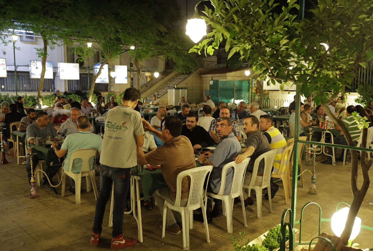 Syrians from Aleppo's Armenian community have dinner at a cafe in the al-Midan neighbourhood of the northern Syrian city on July 5, 2017