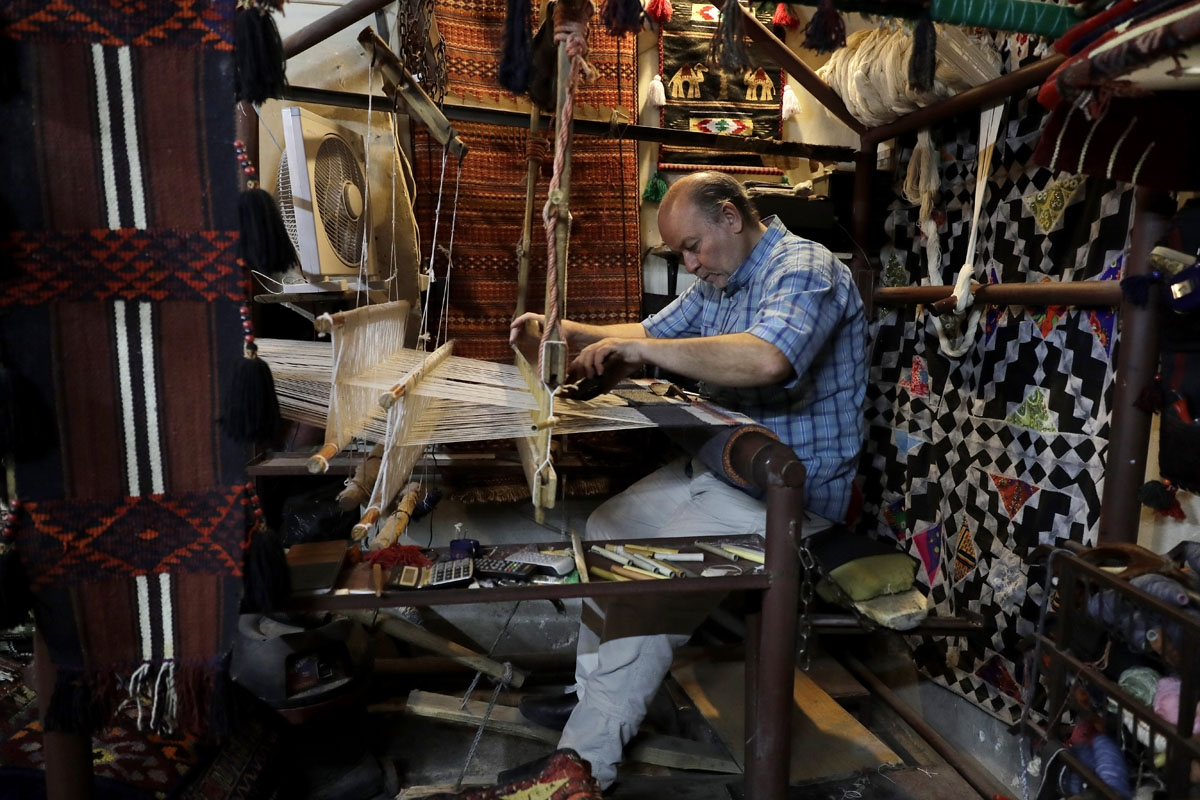 A Syrian artisan sews a handmade rug at his workshop in the capital Damascus on July 9, 2017.