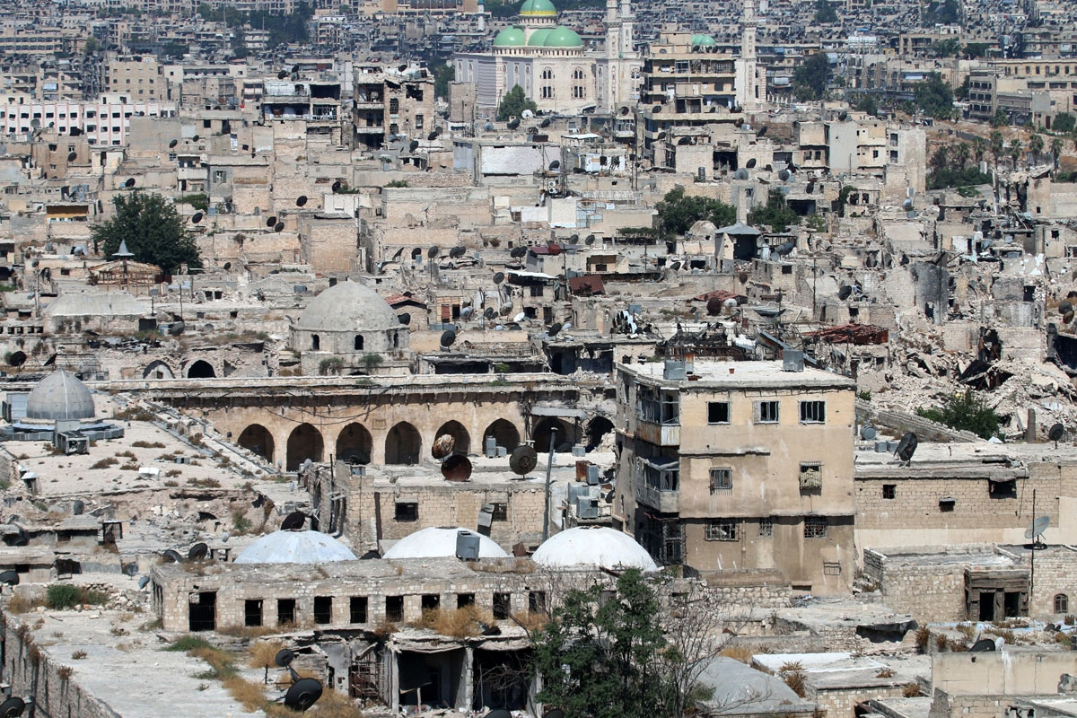 A picture taken on July 3, 2016 from the UNESCO-listed citadel in the government-controlled side of the divided northern Syrian city of Aleppo shows damaged buildings, including the ancient Great Umayyad Mosque (L) at the foot of the medieval fortress.