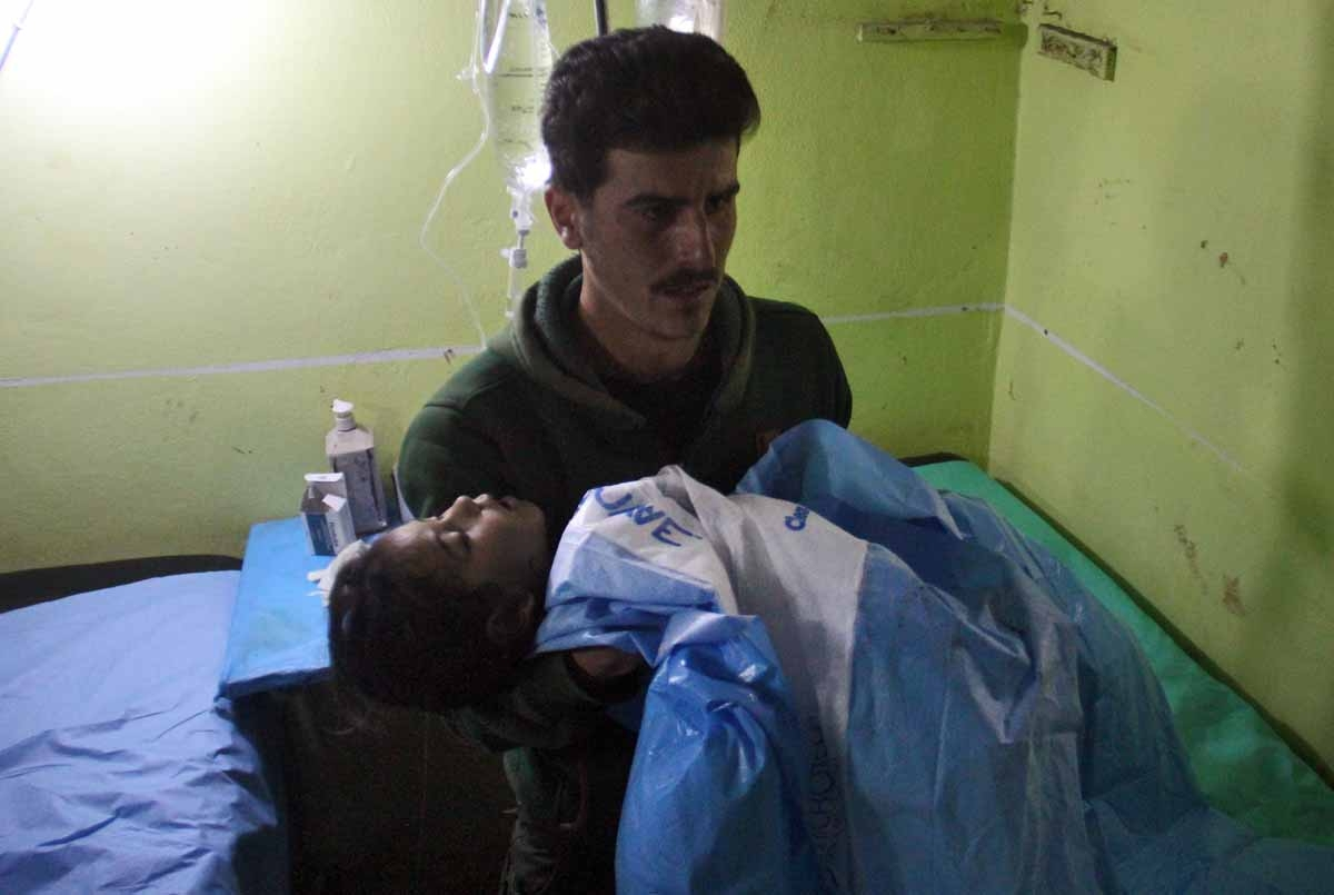 An unconscious Syrian child is carried at a hospital in Khan Sheikhun, a rebel-held town in the northwestern Syrian Idlib province, following a suspected toxic gas attack on April 4, 2017.
