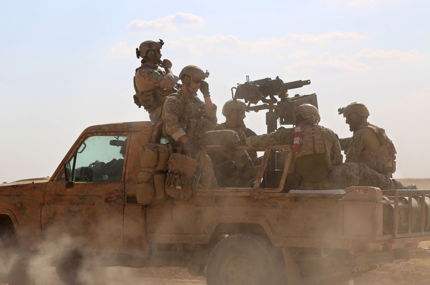 Armed men in uniform identified by Syrian Democratic forces as US special operations forces ride in the back of a pickup truck in the village of Fatisah in the northern Syrian province of Raqa on May 25, 2016.