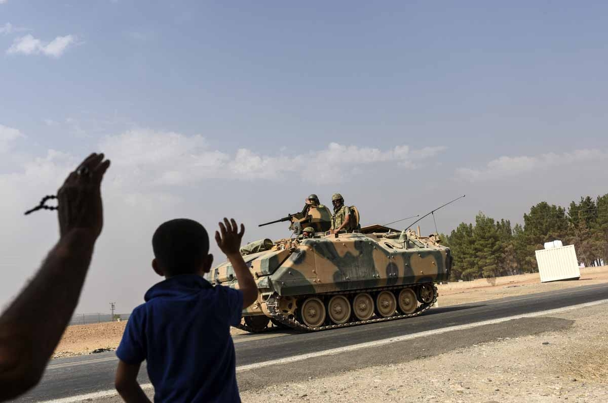 A Turkish boy waves to Turkish tank convoy driving into Syria from the Turkish Syrian border city of Karkamis in the southern region of Gaziantep, on August 26, 2016.