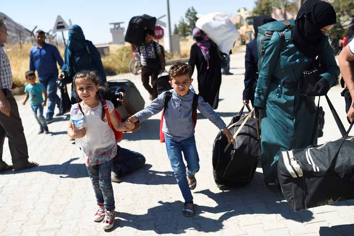 Syrian refugees walk on their way back to the Syrian city of Jarabulus  on September 7, 2016 at Karkamis crossing gate, in the southern region of Kilis.
