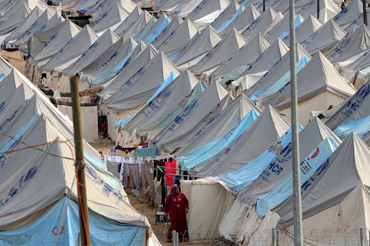 A Syrian refugee woman walks among tents at Karkamis' refugee camp on January 16, 2014 near the town of Gaziantep, south of Turkey.