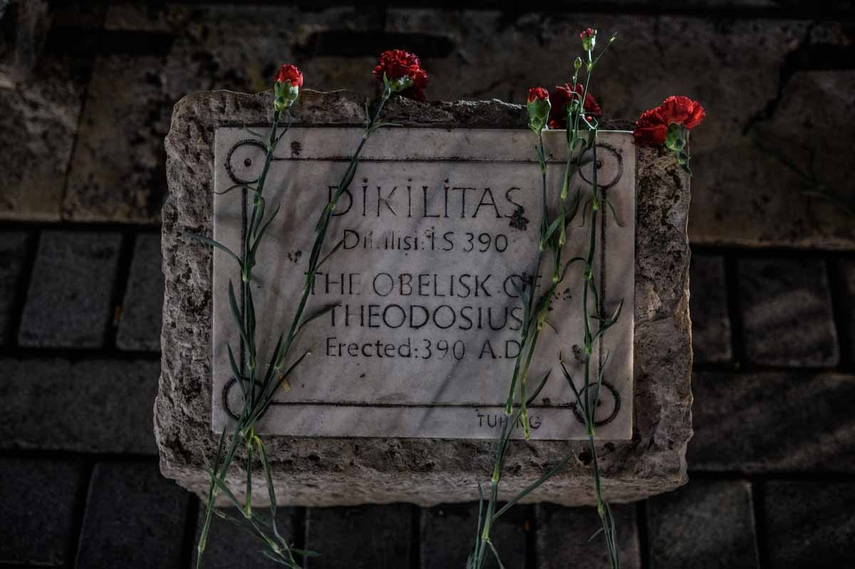 A picture taken on January 13, 2016 shows flowers on a sign stone of  The obelist of Theodosius in tribute to the victims of yesterday deadly attack, on January 13, 2016 on the site of the attack in the Istanbul's tourist hub of Sultanahmet.