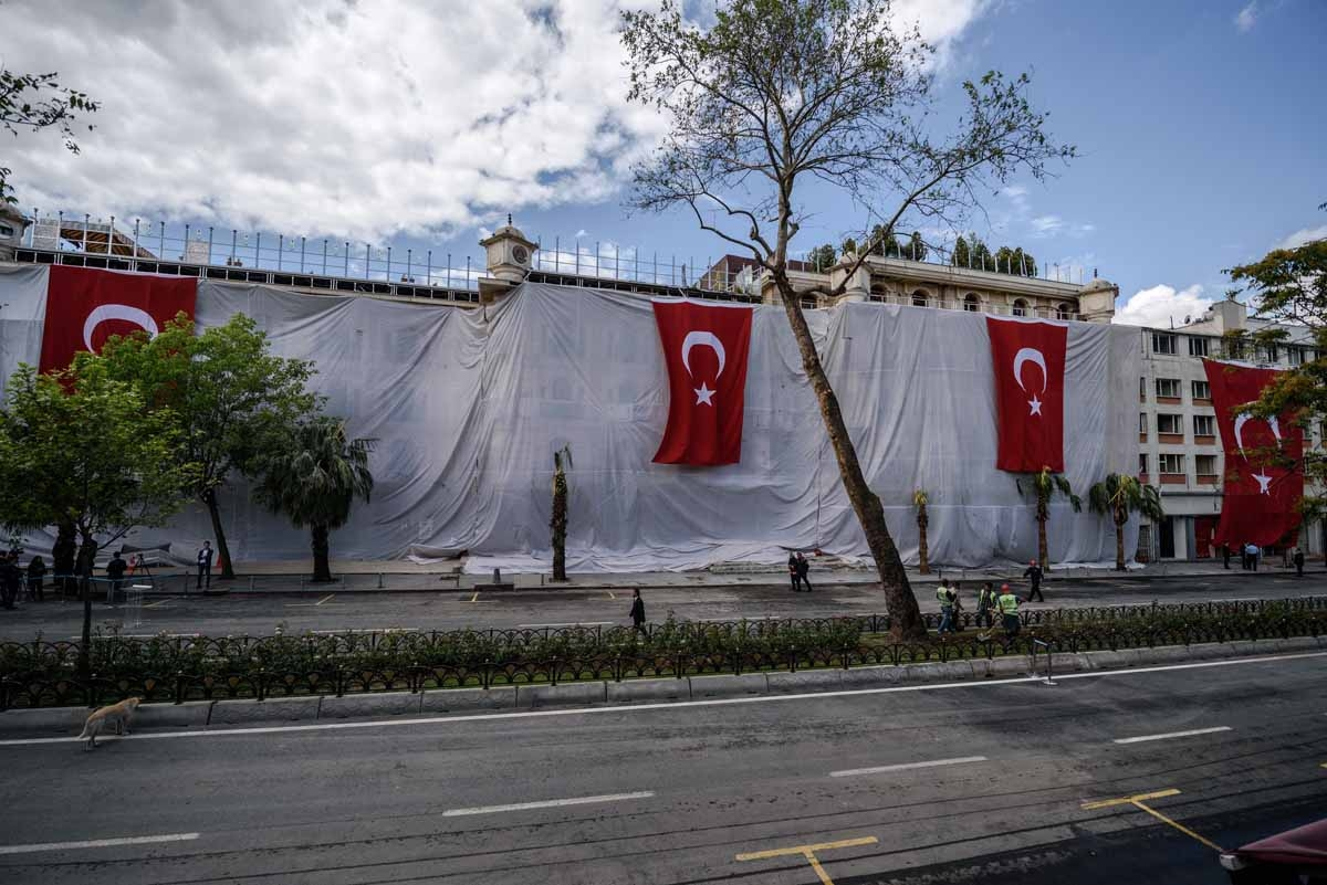 People walk in front of a hotel covered with a tarpaulin and Turkish national flags, a day after a bombing killed 11 people including several police officers, in the Vezneciler district of Istanbul, on June 8, 2016.