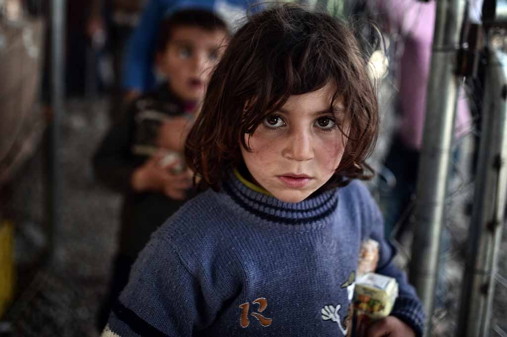 Children queue to receive food on March 6, 2016 in the makeshift camp at the Greek-Macedonian border near the village of Idomeni where thousands of refugees and migrants are stranded on March 6, 2016.