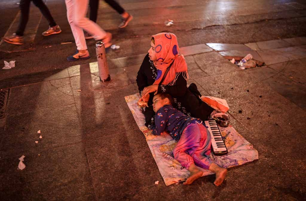 A Syrian refugee woman sits as a child sleeps near her early in the morning on Taksim Square, Istanbul, on May 26, 2015.