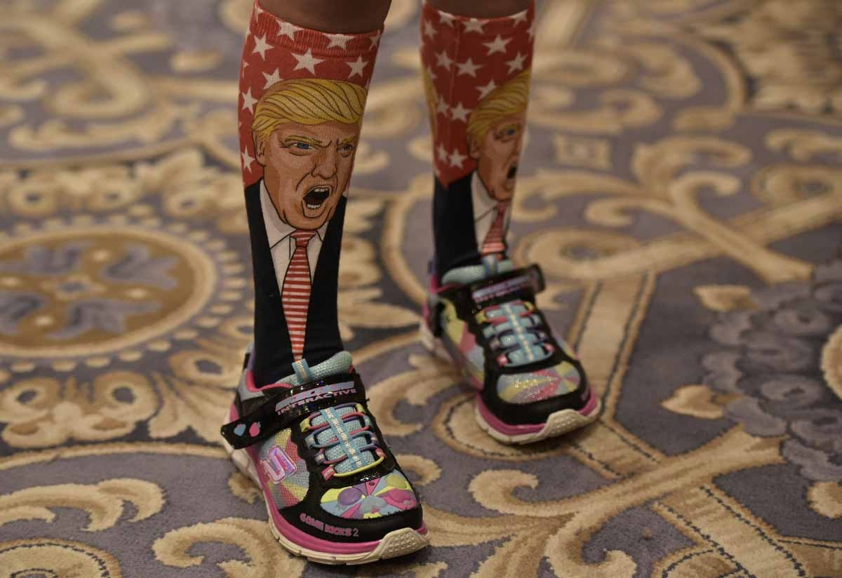 A young supporter wears socks with the image of Republican presidential nominee Donald Trump ahead of his press conference at the Trump International Hotel, in Washington, DC on September 16, 2016.