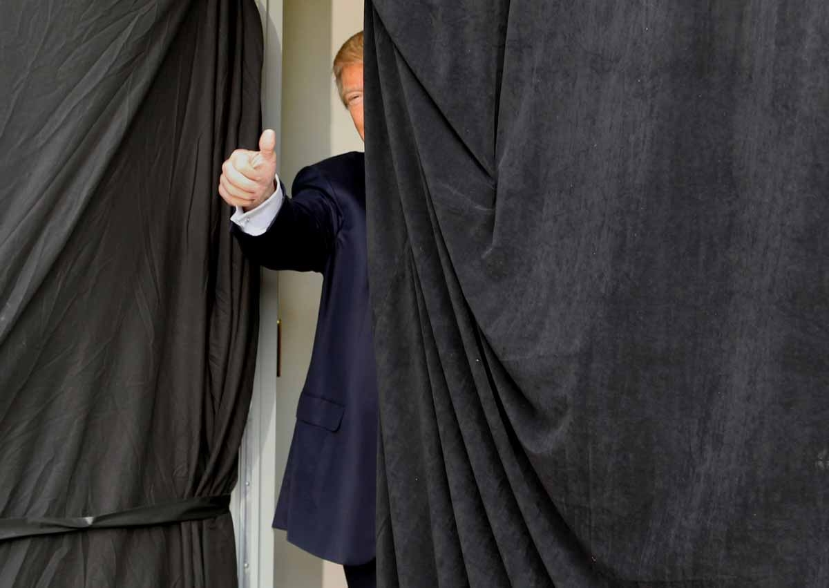 Republican presidential candidate Donald Trump gives a thumbs up from behind the curtain before taking the stage at an event on October 15, 2016 in Portsmouth, New Hampshire.