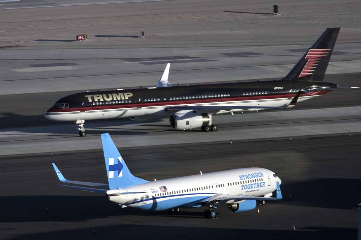 Republican presidential nominee Donald Trump's plane (TOP) passes Democratic presidential nominee Hillary Clinton's campaign plane at McCarran International Airport on October 18, 2016 in Las Vegas, Nevada, on the eve of the two candidates' third and fina