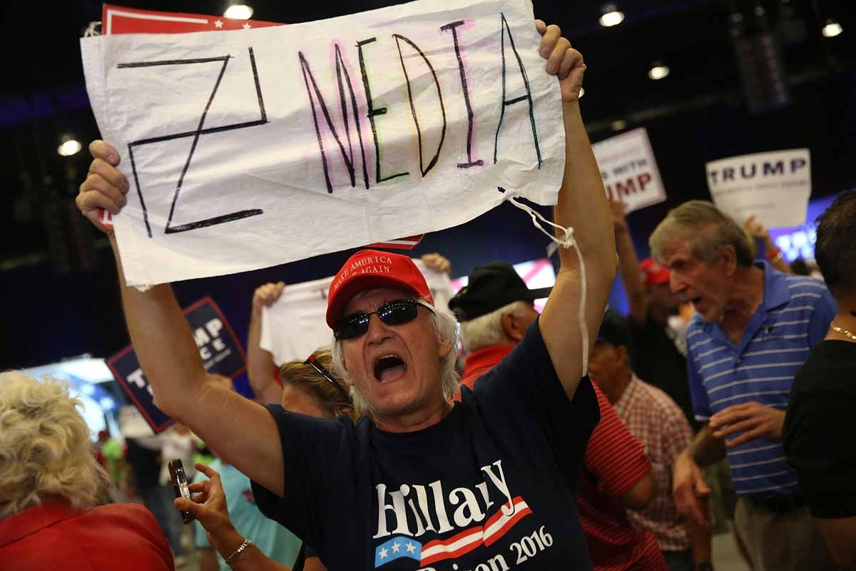 A man holds a sign towards the media as he attends a campaign rally for Republican presidential candidate Donald Trump at the South Florida Fair Expo Center on October 13, 2016 in West Palm Beach, Florida.