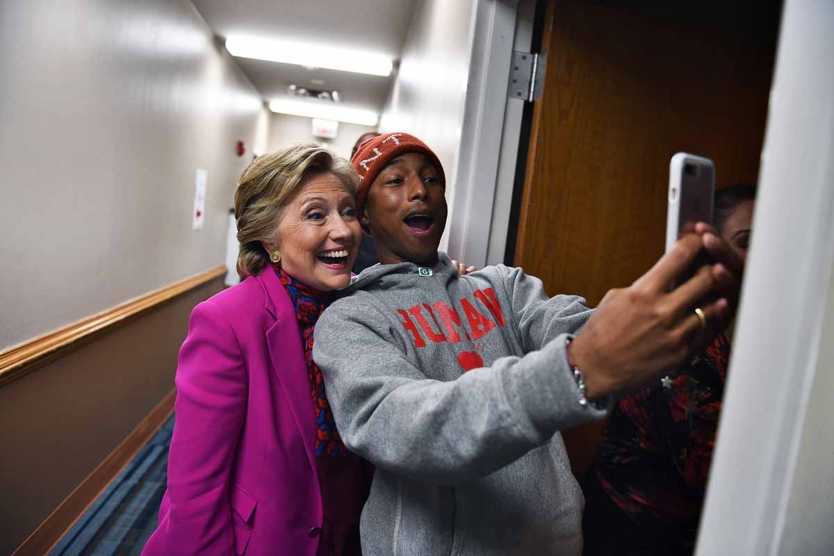 US Democratic presidential nominee Hillary Clinton poses with singer Pharrell Williams for a selfie backstage before a campaign rally in Raleigh, North Carolina, on November 3, 2016.