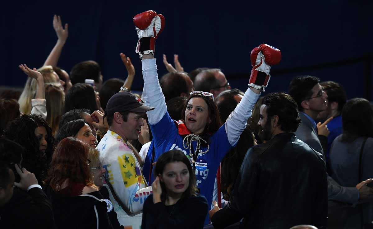 A supporter of Democratic presidential nominee Hillary Clinton raises her arms with boxing gloves on during election night at the Jacob K. Javits Convention Center in New York on November 8, 2016.