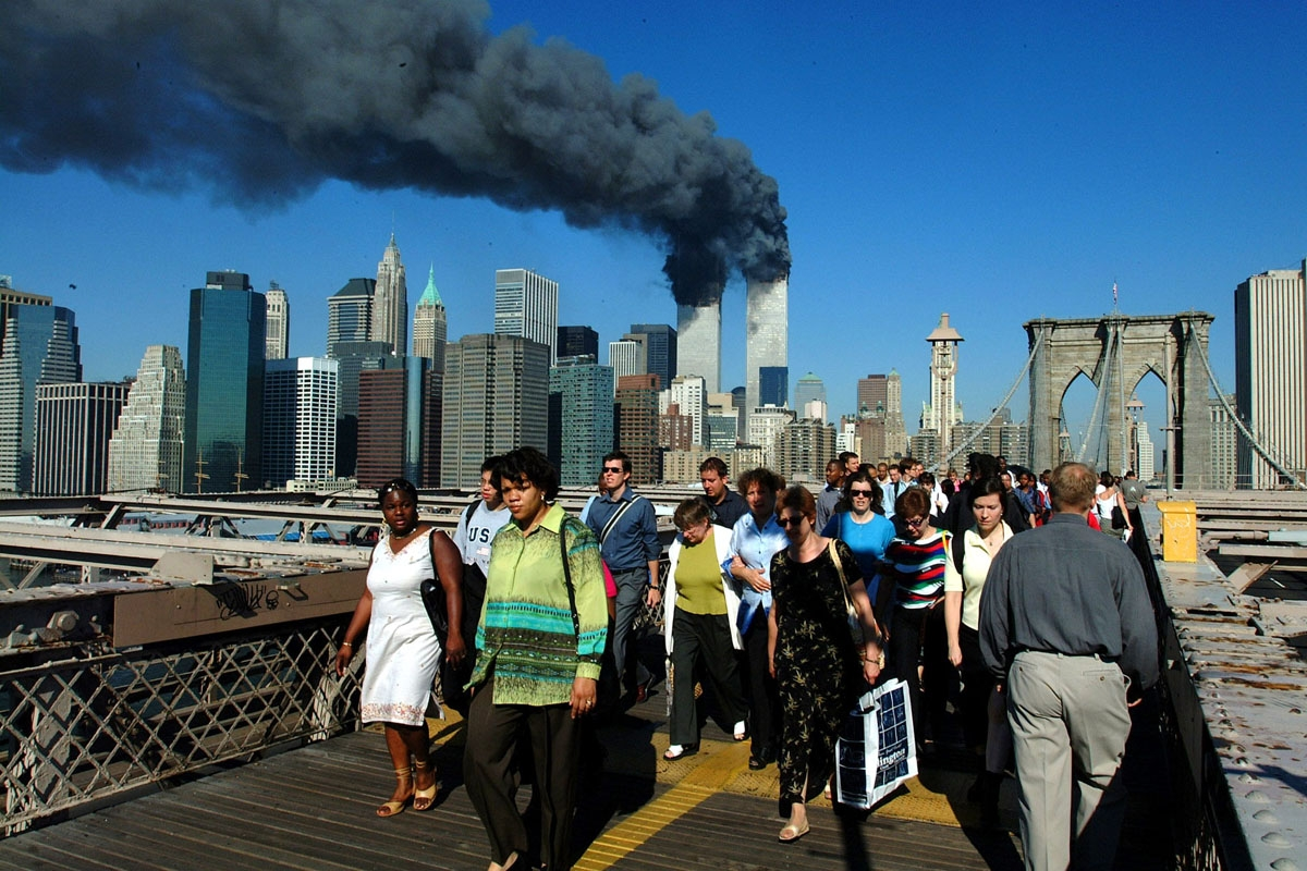 Pedestrians walk across the Brooklyn Bridge away from the burning World Trade towers before their collapse 11 September, 2001