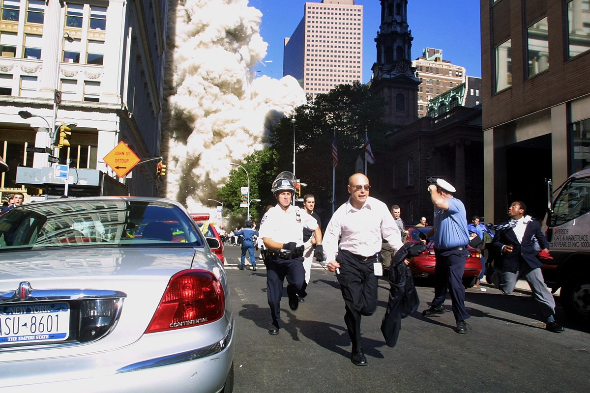 Police and pedestrians run for cover during the first collapse of the World Trade Center Tower after the landmark skyscrapers were struck by two hijacked airplanes 11 September 2001