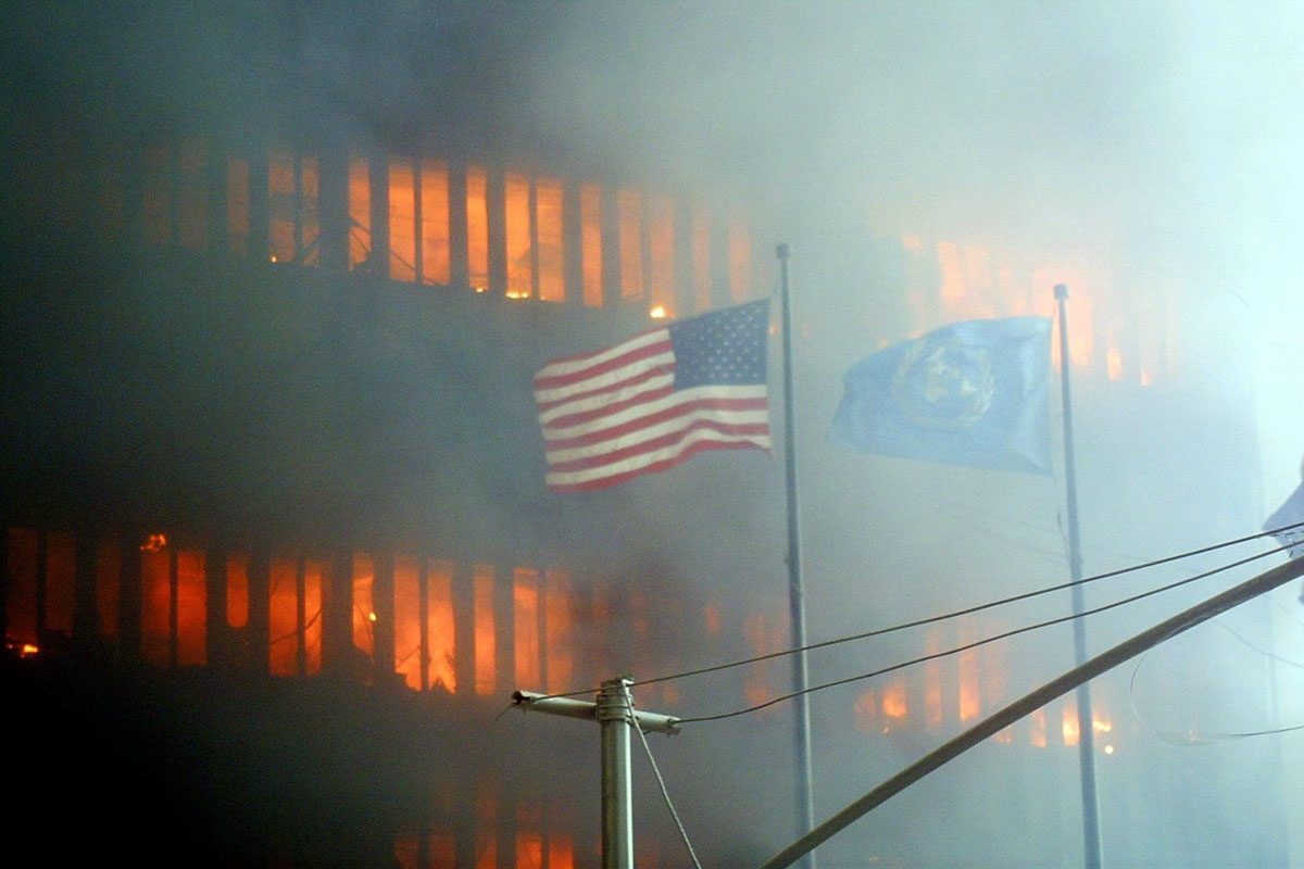 An American flag flies in the foreground as one of the World Trade Center towers burns in the background 11 September 2001 in New York.