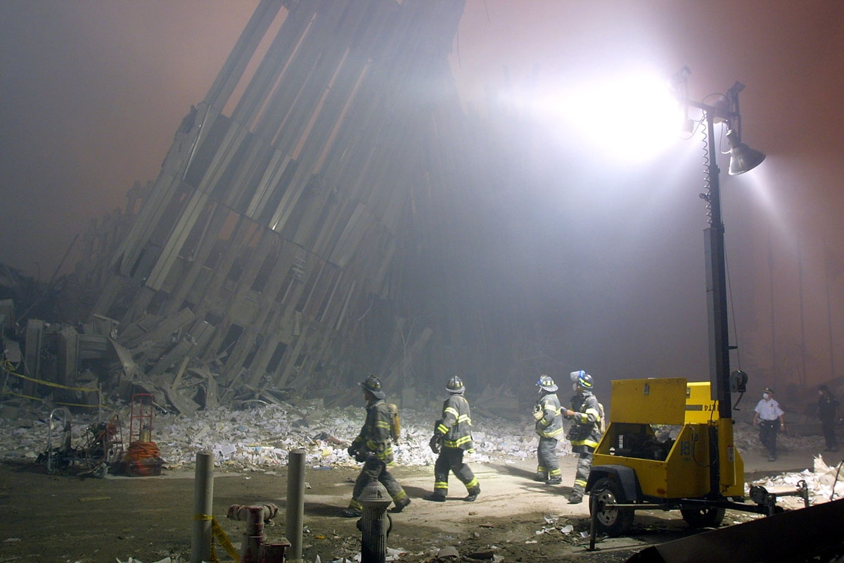 Firefighters make their way through the rubble of the World Trade Center 11 September 2001