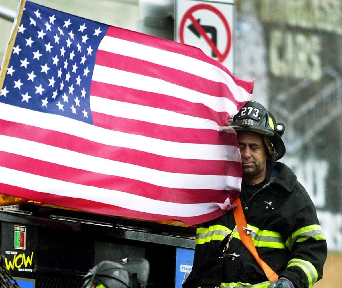 A tired fireman rests as he rides on the back of a flatbed truck 14 September 2001 in New York.