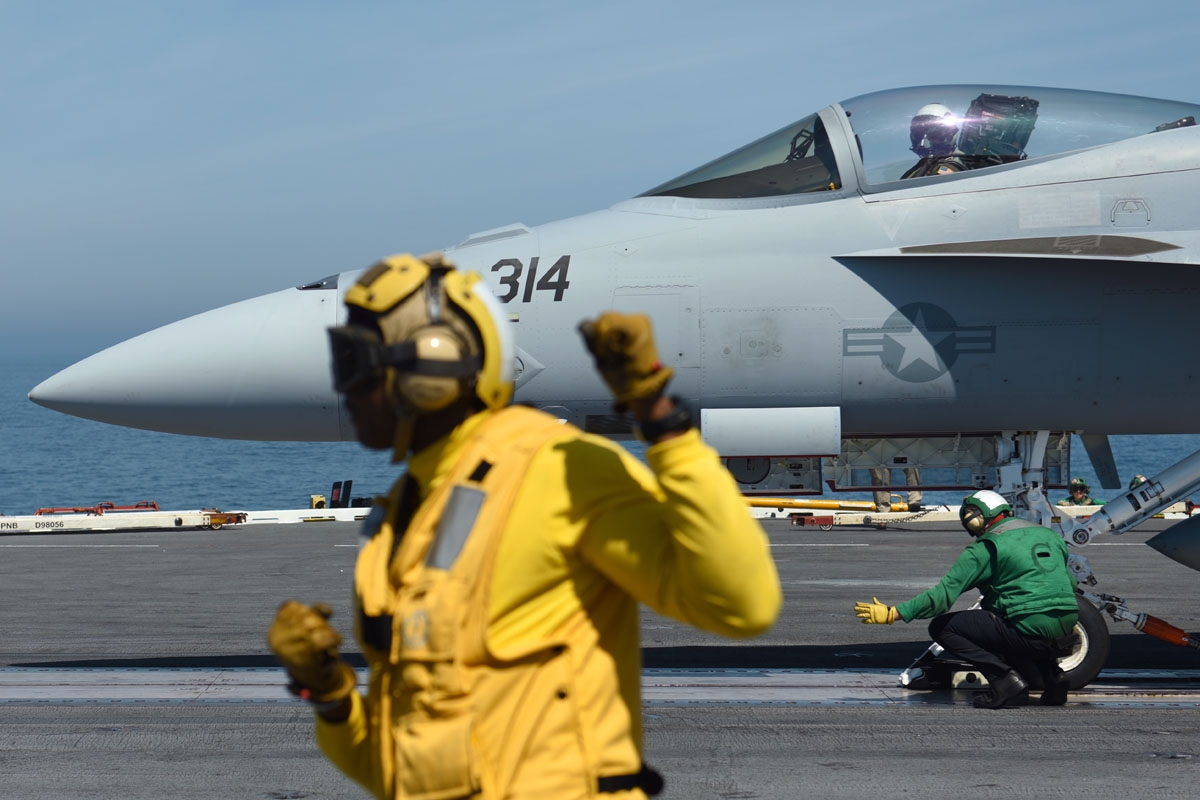 Le Catapult officer Nigel (L) gestures as a US Navy F/18 Hornet jet is catapulted off the USS George H.W. Bush aircraft carrier on May 11, 2018 in the Atlantic Ocean.