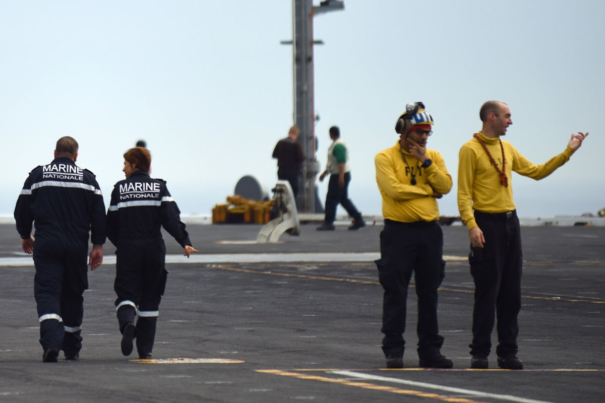 French Navy personnel (L) walk past US catapult officers on the  deck of the USS George H.W. Bush aircraft carrier on May 12, 2018 in the Atlantic Ocean.