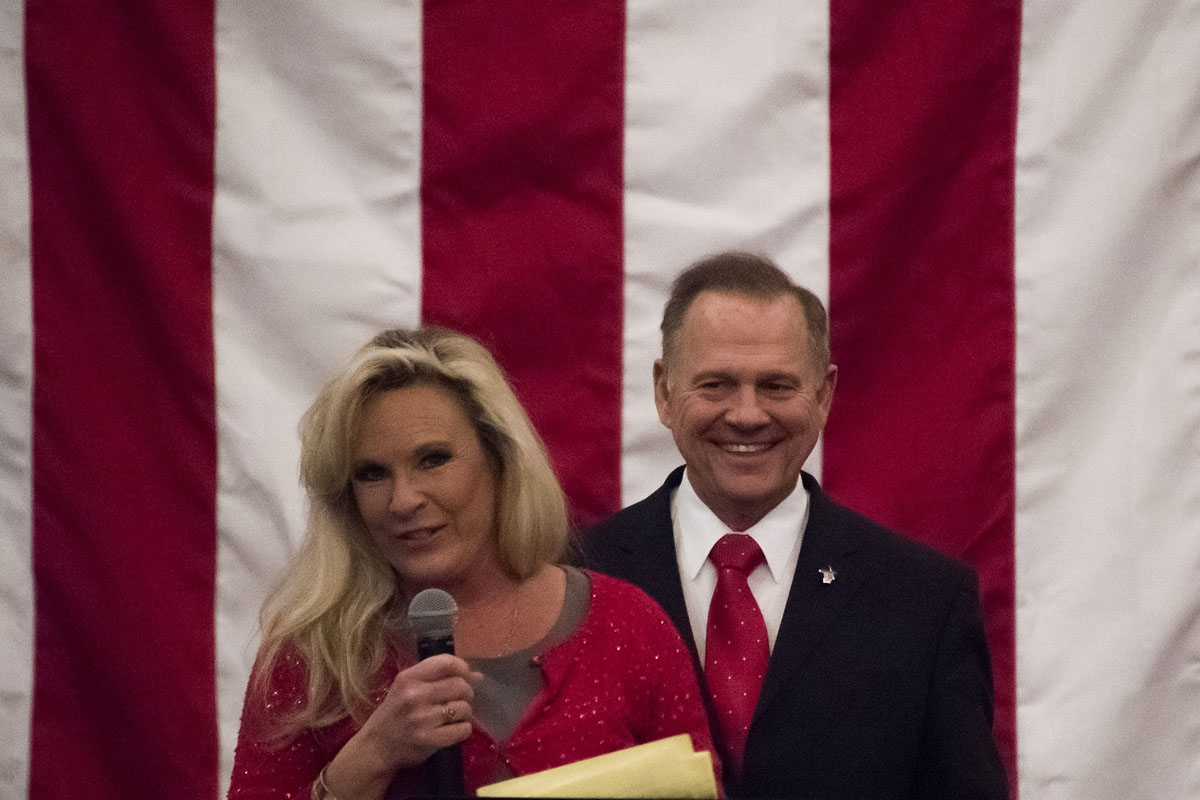 Republican Senatorial candidate Roy Moore smiles as his wife Kayla speaks at a rally in Midland, Alabama, on December 11, 2017