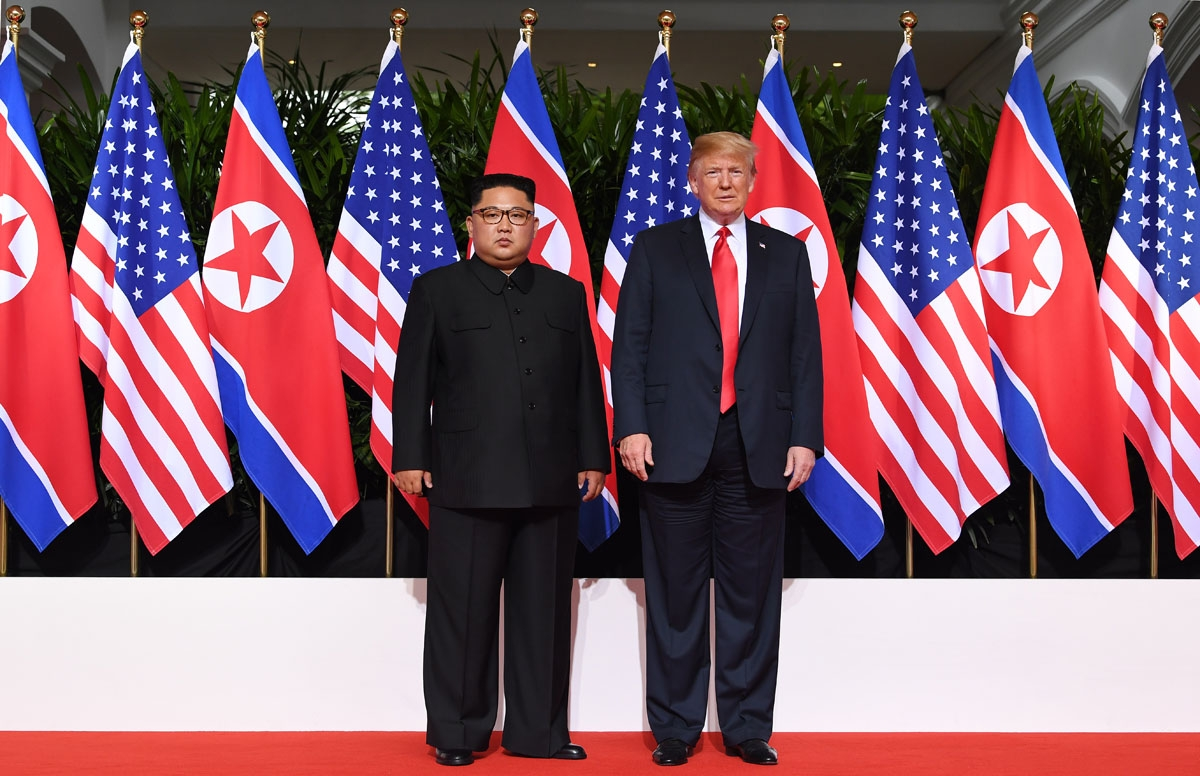 US President Donald Trump (R) poses with North Korea's leader Kim Jong Un (L) at the start of their historic US-North Korea summit, at the Capella Hotel on Sentosa island in Singapore on June 12, 2018.