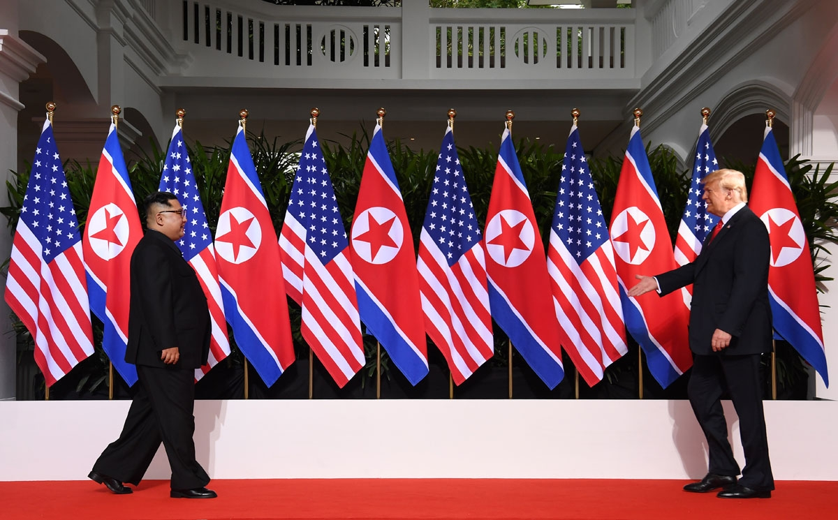 US President Donald Trump (R) and North Korea's leader Kim Jong Un (L) walk toward one another at the start of their historic US-North Korea summit, at the Capella Hotel on Sentosa island in Singapore on June 12, 2018.