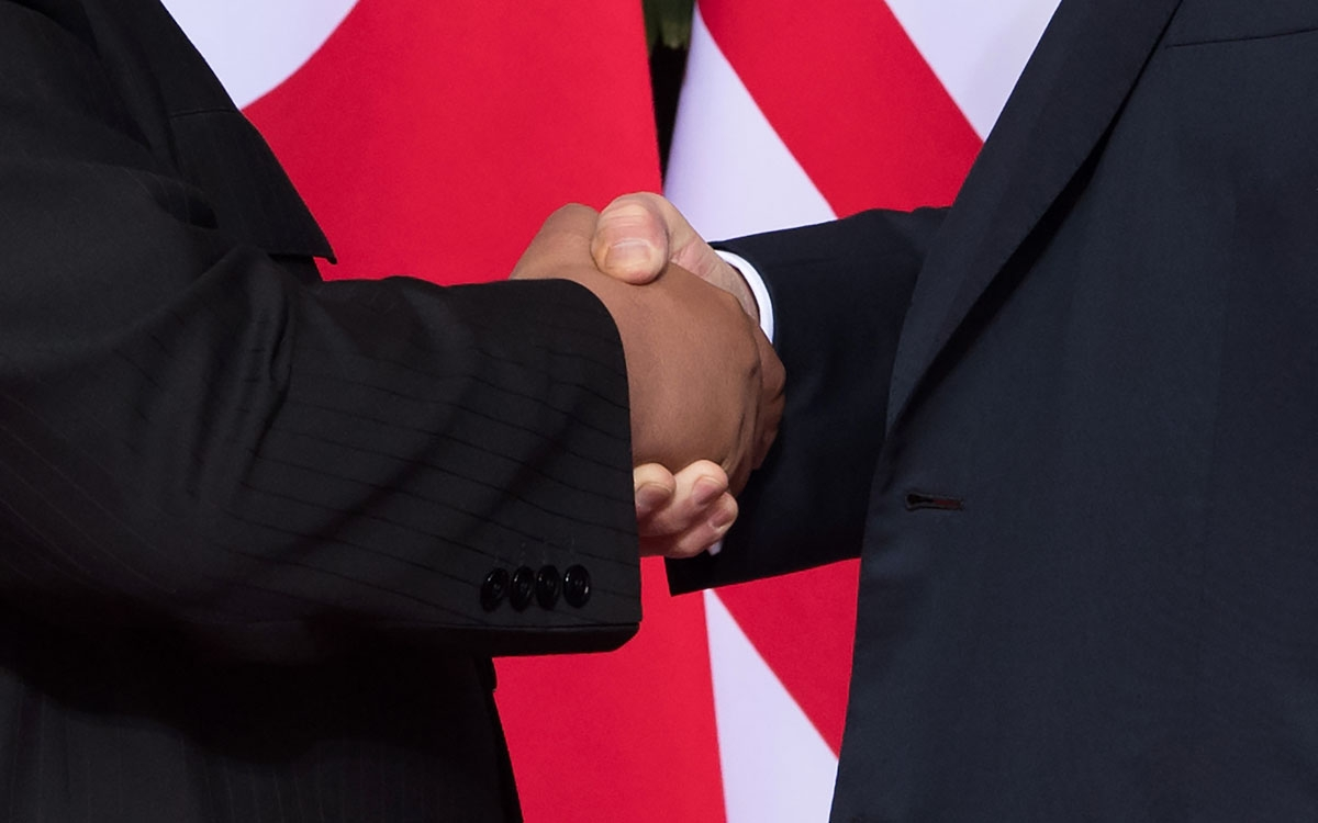 US President Donald Trump (R) shakes hands with North Korea's leader Kim Jong Un (L) at the start of their historic US-North Korea summit, at the Capella Hotel on Sentosa island in Singapore on June 12, 2018.