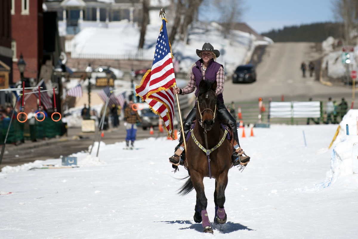 Flag bearer Jesslyn Swirka rides her horse down Harrison Avenue in Leadville, Colorado at the start of the 68th annual Leadville Ski Joring weekend competition on Saturday, March 4, 2017 in Leadville, Colorado.