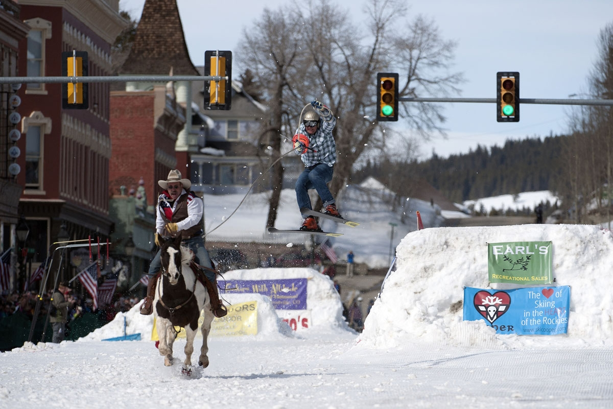 Rider Jeff Dahl races down Harrison Avenue while skier and son Greg Dahl airs out off the final jump of the Leadville skijoring course during the 68th annual Leadville Ski Joring weekend competition on Saturday, March 4, 2017 in Leadville, Colorado.