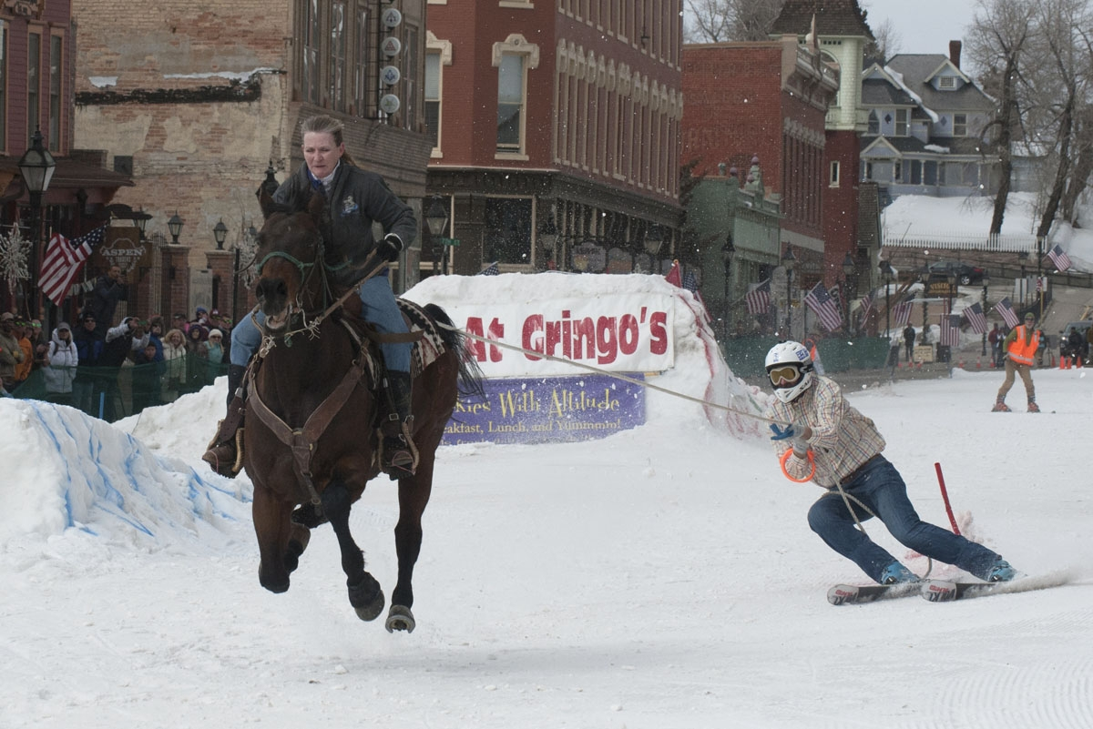 Rider Dana Stiles races down Harrison Avenue towing skier Mike Fries during the 68th annual Leadville Ski Joring weekend competition on March 5, 2017 in Leadville, Colorado.