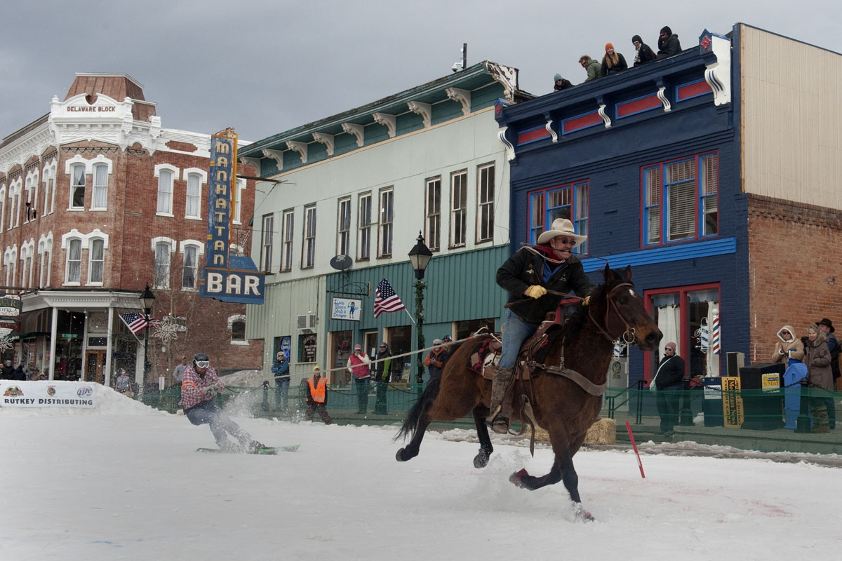 Rider Jeff Dahl races down Harrison Avenue towing skier and son Jason Dahl  during the 68th annual Leadville Ski Joring weekend competition on March 5, 2017 in Leadville, Colorado.