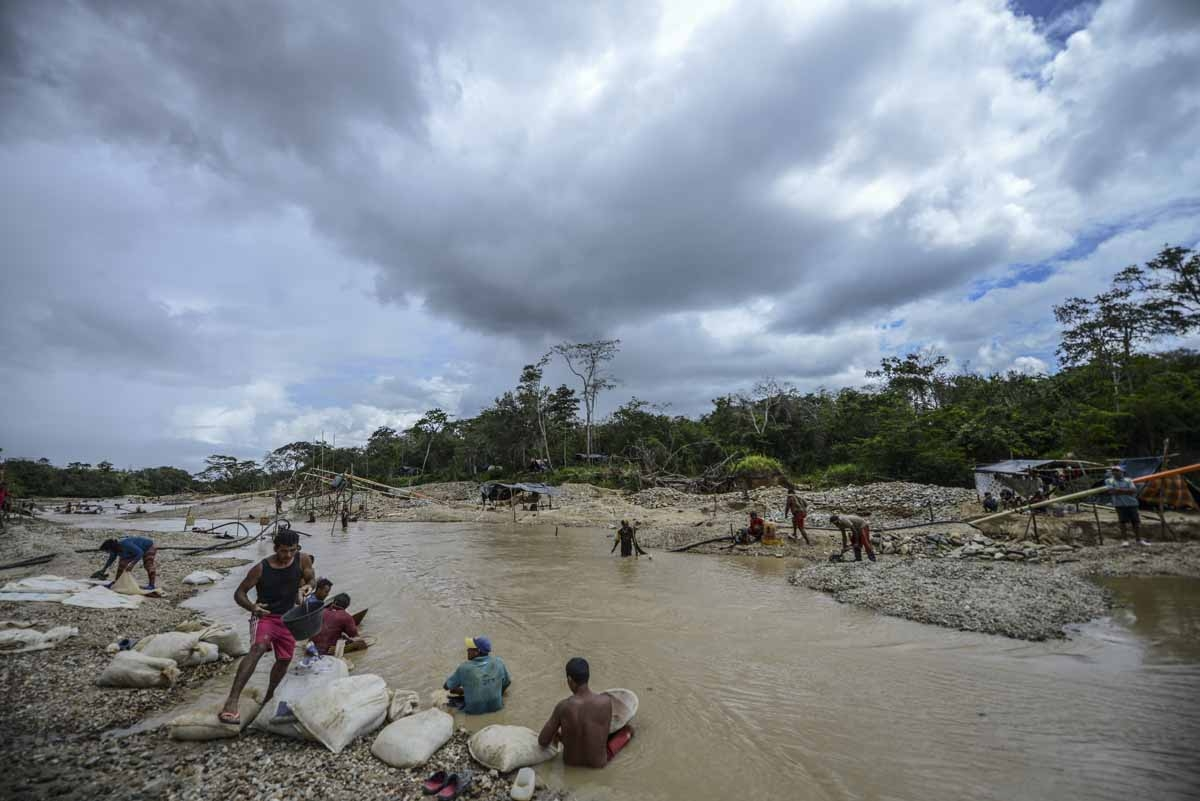 Men work at Nacupay gold mine on the banks of a river in El Callao, Bolivar state, southeastern Venezuela on February 24, 2017. Although life in the mines of eastern Venezuela is hard and dangerous, tens of thousands from all over the country head for the