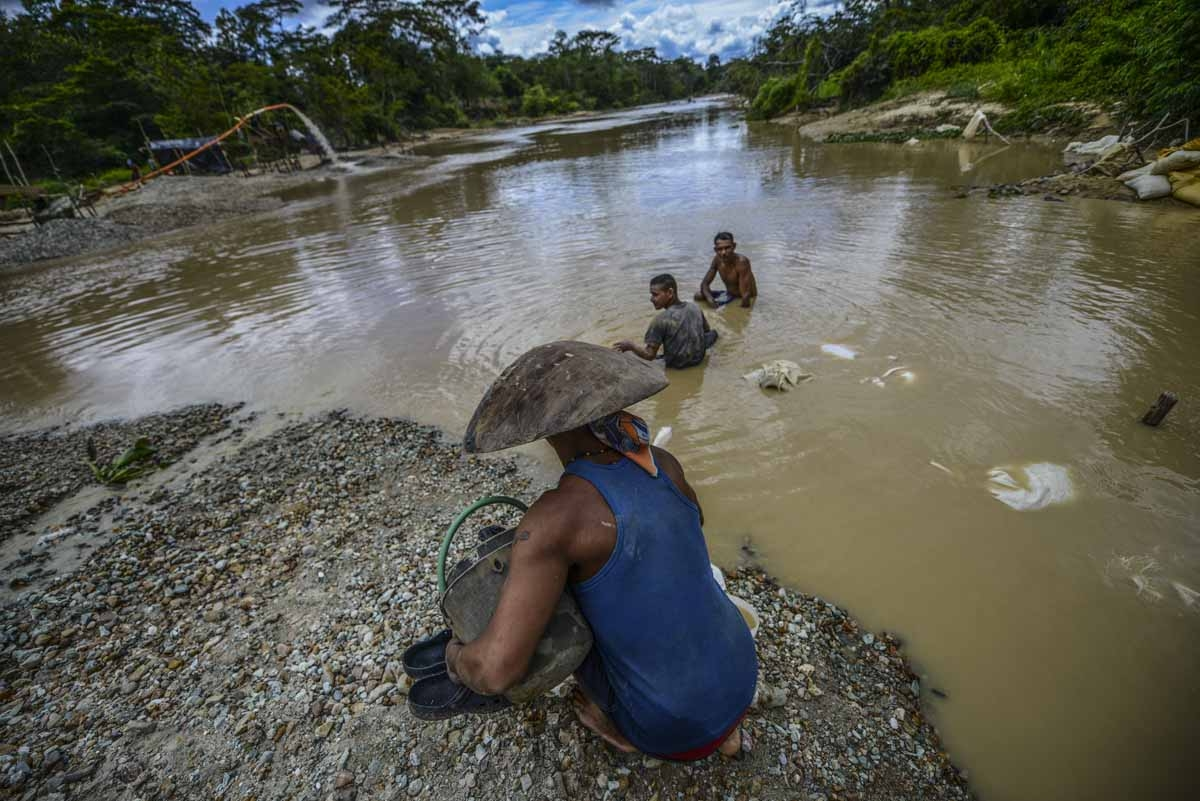 Men work at Nacupay gold mine on the bank of a river in El Callao, Bolivar state, southeastern Venezuela on February 24, 2017.