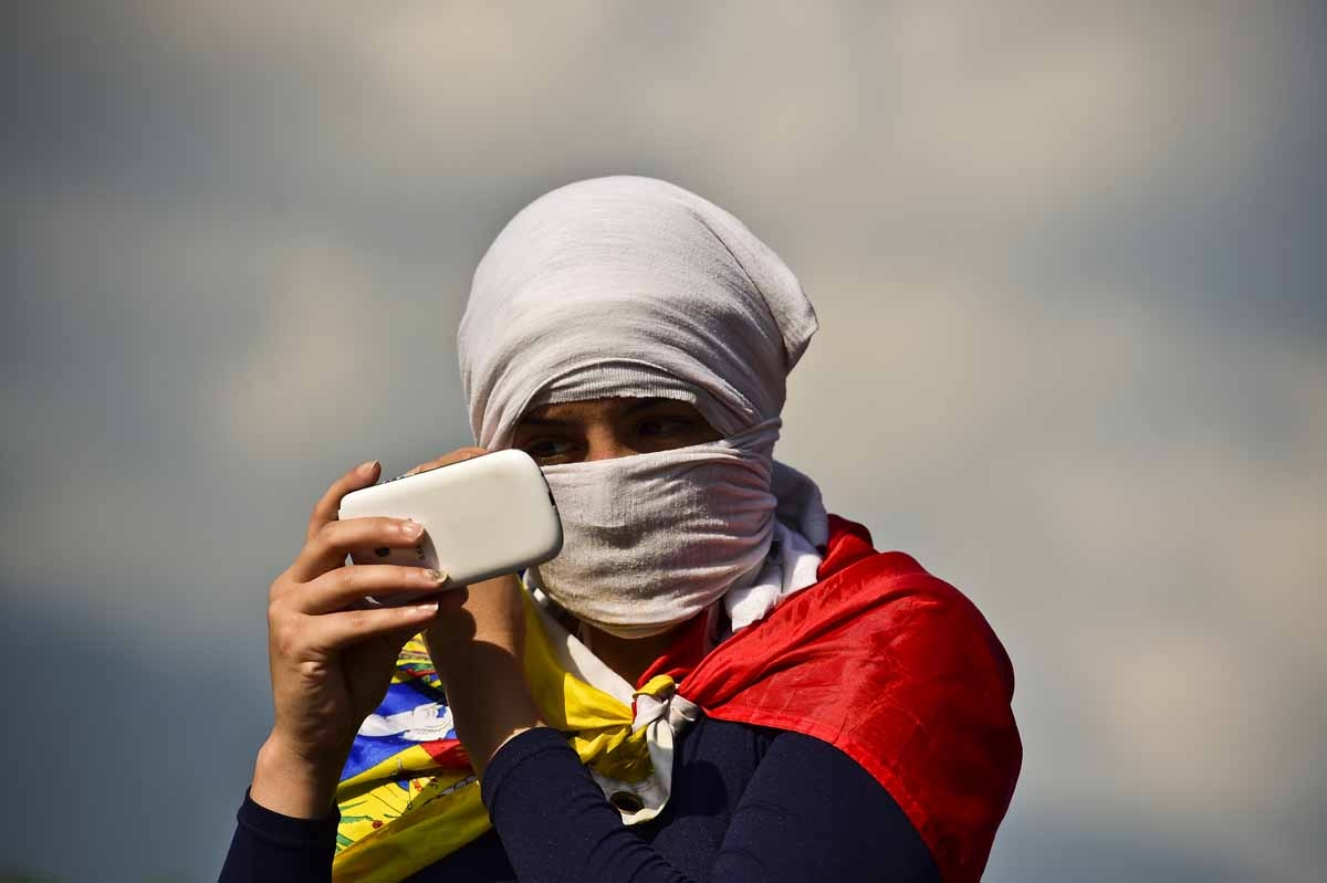 A masked Venezuelan opposition activist uses her cell-phone during a demonstration against Venezuelan President Nicolas Maduro in Caracas, on April 24, 2017.
